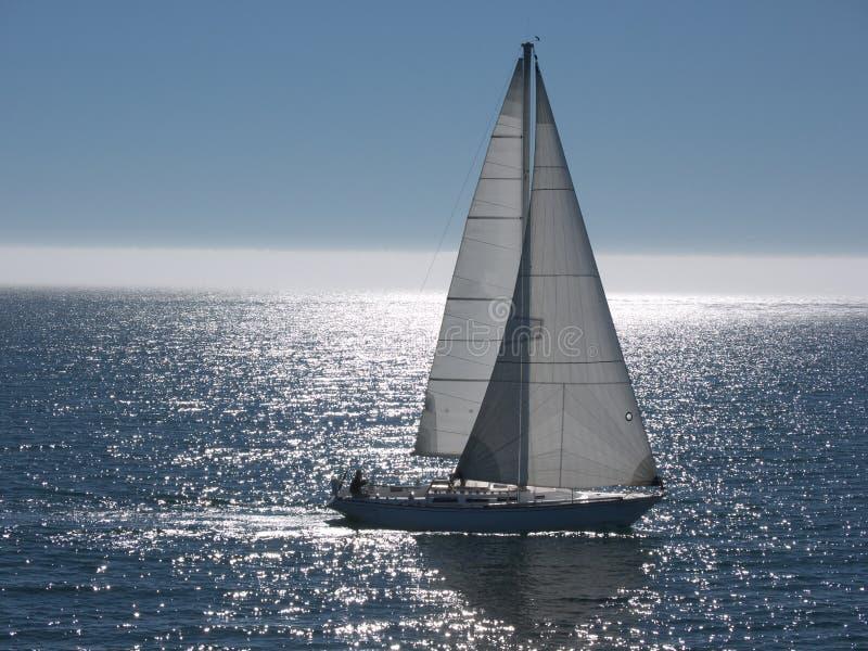 Bateau à voiles glissant sur la mer calme image libre de droits