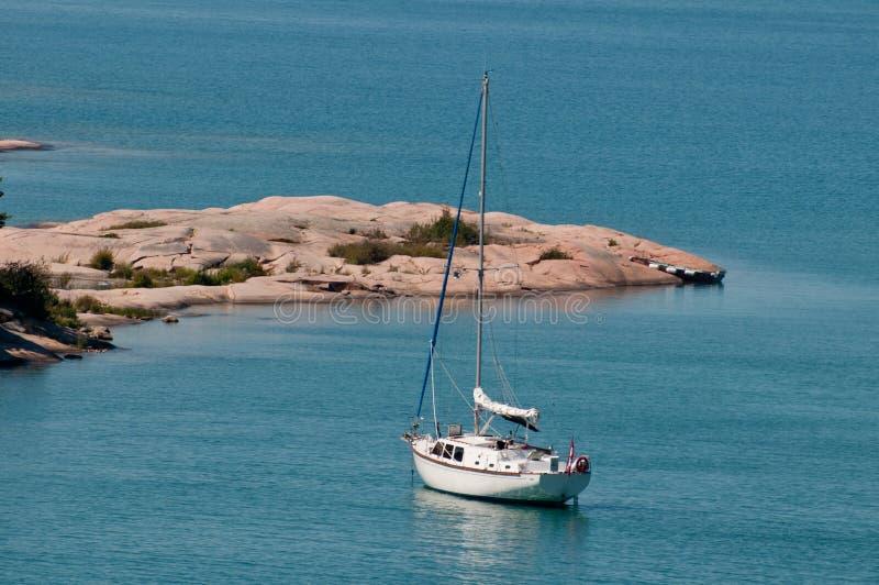Bateau à voiles près d'un rivage rocheux images libres de droits