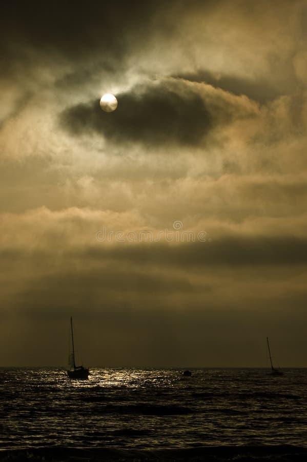 Bateau à voiles sur un ciel menaçant images libres de droits