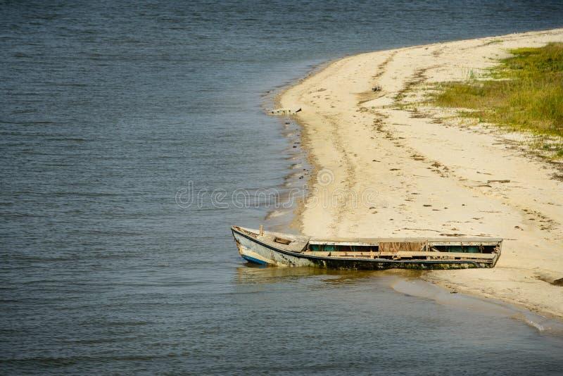Bateau abandonné d'huître sur la plage photos stock