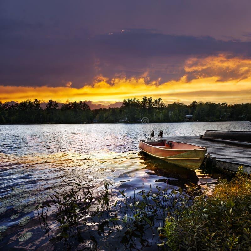 Bateau accouplé sur le lac au coucher du soleil image libre de droits