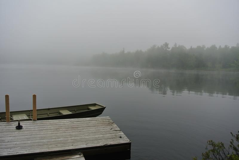 Bateau accouplé sur le lac brumeux images libres de droits