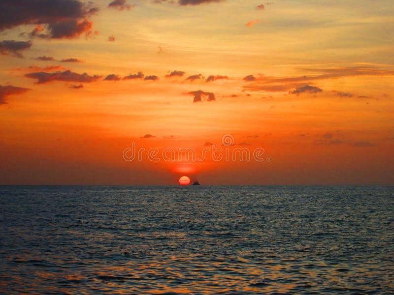 Bateau au coucher du soleil sur la plage photographie stock libre de droits