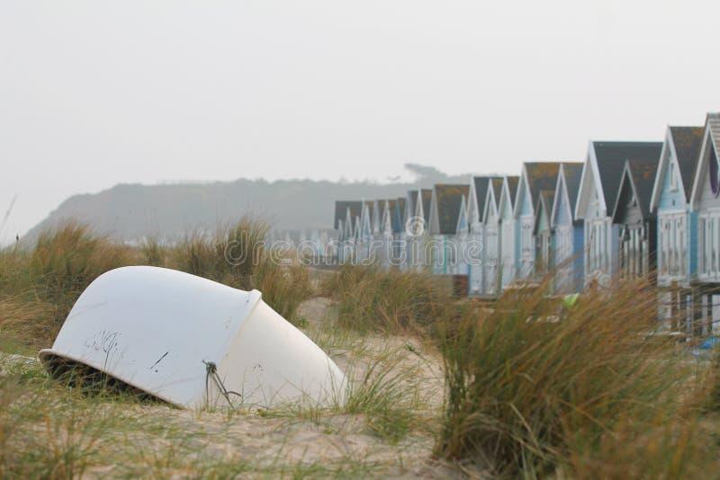 Bateau avec des huttes de plage chez Mudeford, Dorset, R-U photographie stock