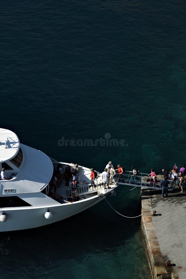 Bateau avec les touristes qui débarquent dans Vernazza, village de Cinque Terre Débarquement des touristes en mer bleue profonde photos libres de droits