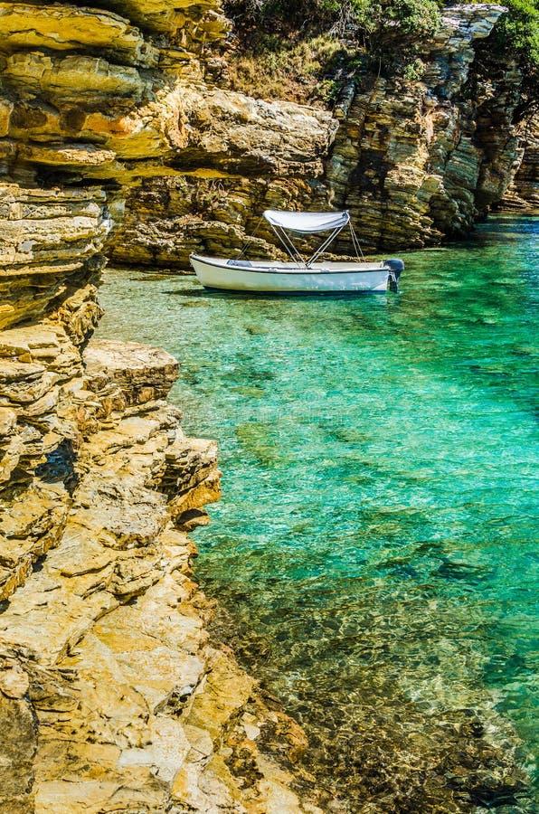 Bateau blanc dans la petite baie azurée mignonne entourée par des falaises de pierre de chaux en île de Corfou, Grèce photos libres de droits