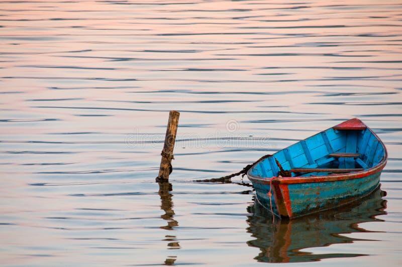 Bateau dans l'eau crépusculaire du lac Phewa photos stock