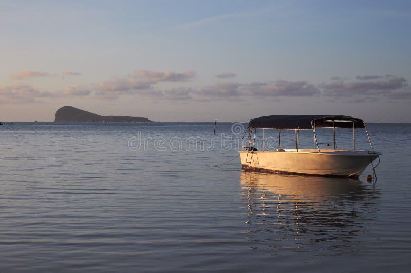Bateau dans l'océan au coucher du soleil photo libre de droits