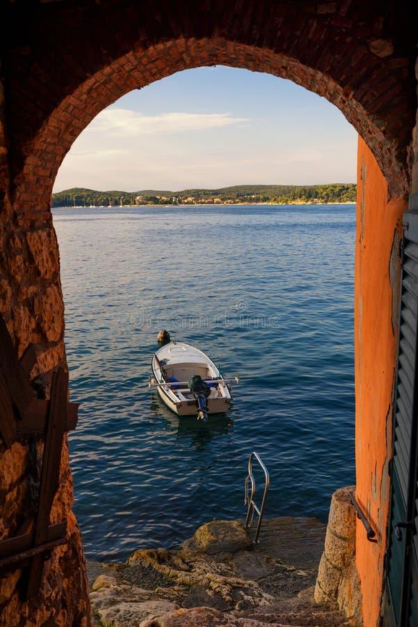 Bateau dans la mer Adriatique vu depuis la paroi voûtée de Rovinj au coucher du soleil, péninsule Istrique, Croatie image stock