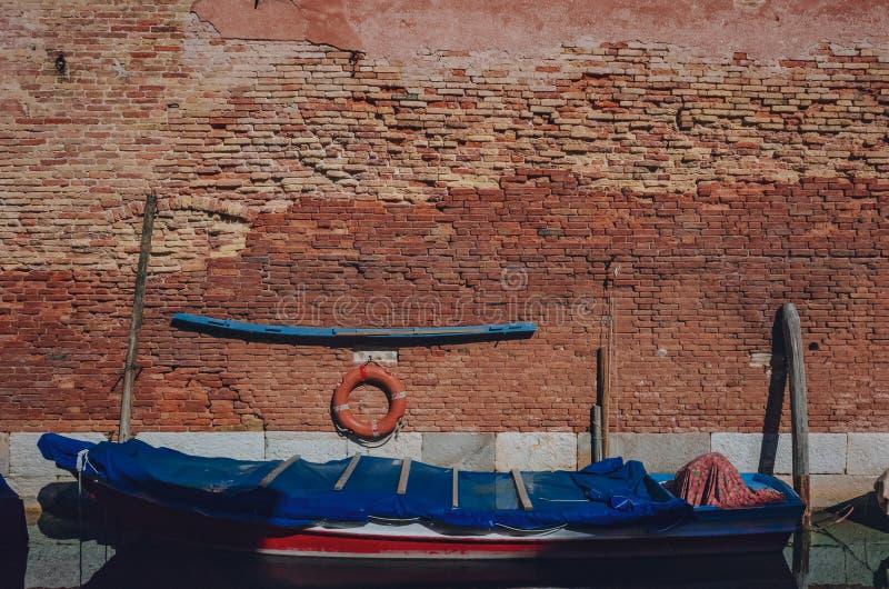Bateau dans le canal par un vieux mur de briques rouge-brun, à Venise, l'Italie photographie stock