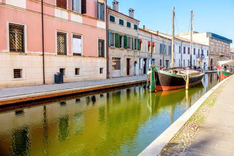 Bateau dans un canal du village italien coloré de Comacchio dedans photos libres de droits