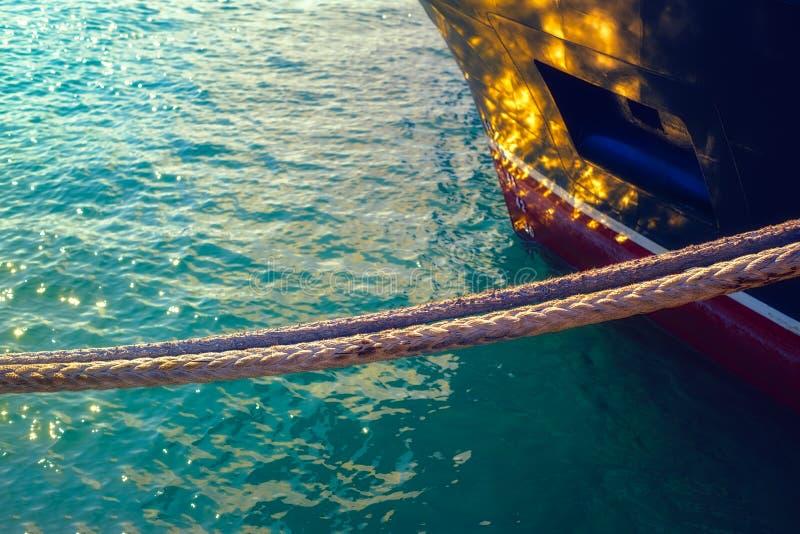 Bateau de corde de haussière accrochant au-dessus de l'eau avec le soleil rougeoyant photo libre de droits