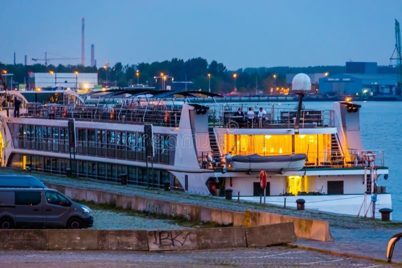 Bateau de croisière accouplé au port de la ville d'Anvers, paysage allumé de ville par la nuit, quai d'Antwerpen, Belgique photo stock