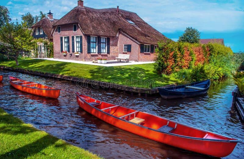 Bateau de deux rouges dans le canal de Giethoorn image libre de droits