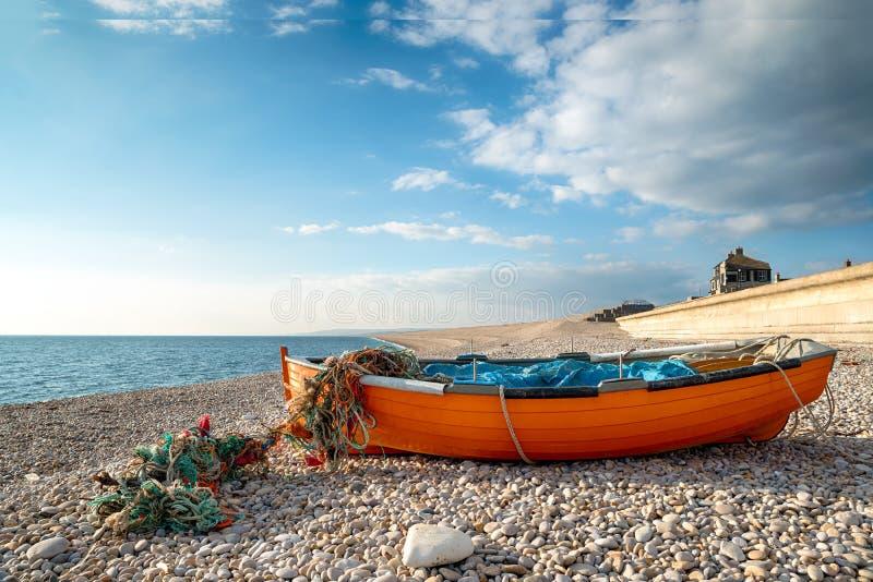 Bateau de Fisning sur la plage de Chesil image stock