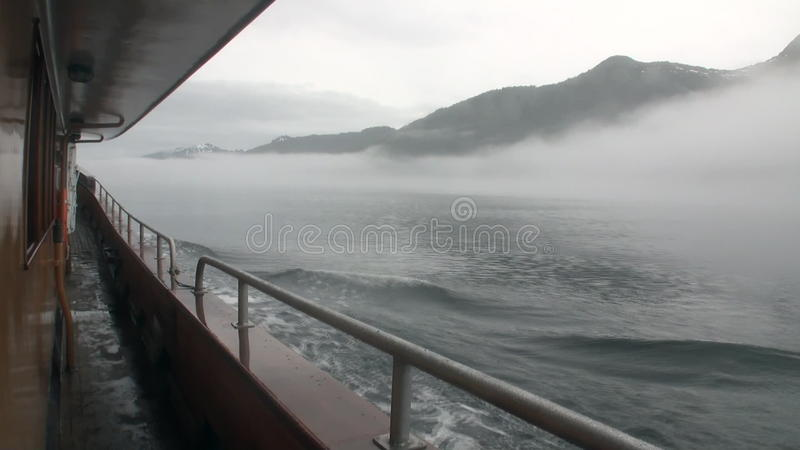 Bateau de flanc en brouillard sur l'eau de l'océan pacifique sur des montagnes Alaska de fond banque de vidéos