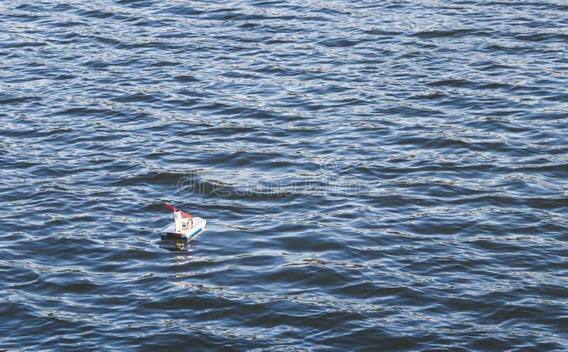 Bateau de jouet flottant sur la surface du lac photographie stock