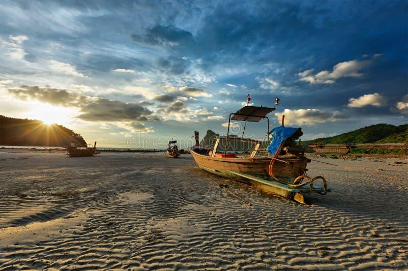 Bateau de long arrière sur la plage sur le coucher du soleil, Thaïlande photographie stock libre de droits