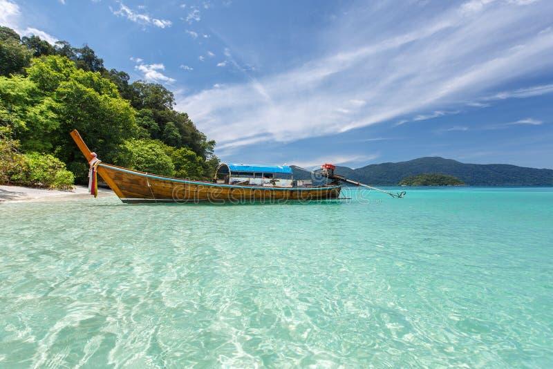 Bateau de Longtail sur la mer clair comme de l'eau de roche à la plage tropicale photo stock