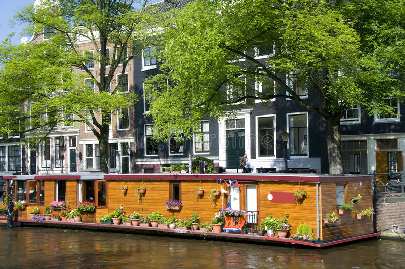 Bateau de maison de canal d'Amsterdam Hollande avec des fleurs images stock