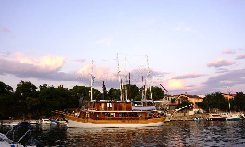 Bateau de navigation de touristes de cru complètement de touristes ancré dans le port maritime devant le bord de mer photographie stock libre de droits