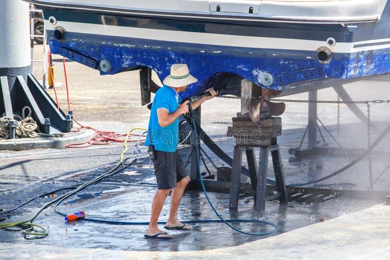 Bateau de nettoyage d'homme avec de l'eau à haute pression image libre de droits