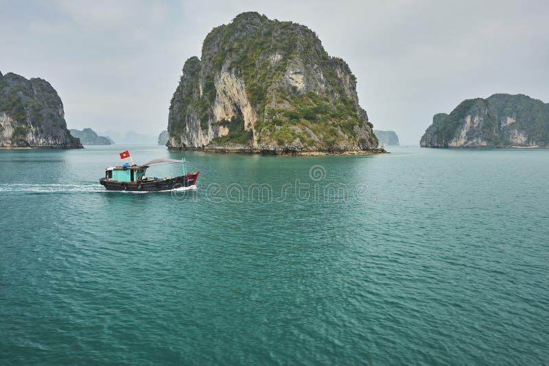Bateau de pêche à travers la baie long d'ha images stock