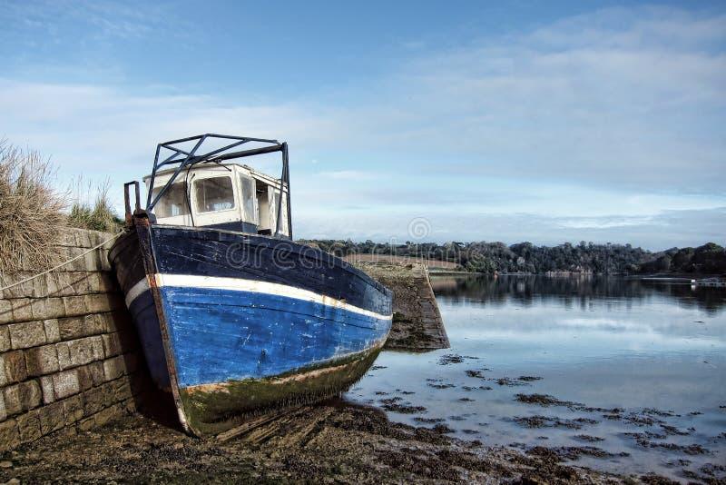 Bateau de pêche abandonné au dock à marée basse photographie stock