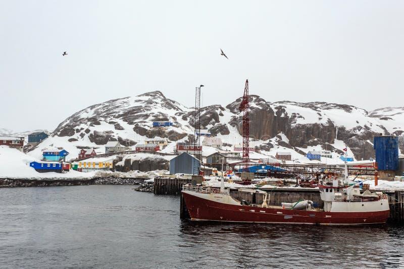 Bateau de pêche au pilier du village de Maniitsoq avec hous coloré images stock