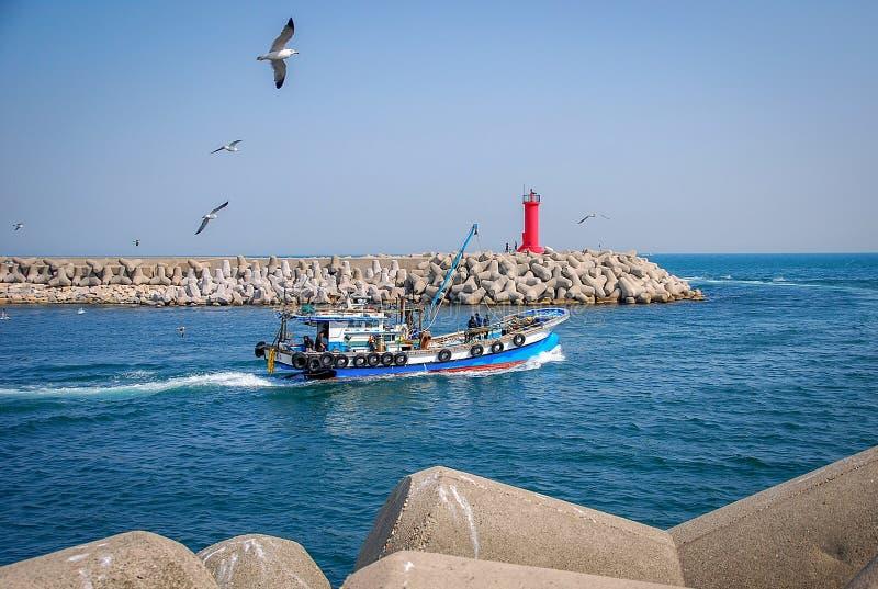 Bateau de pêche avec des pêcheurs quittant le port photo libre de droits