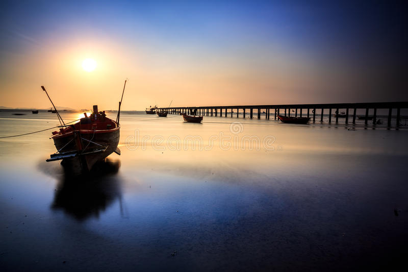 Bateau de pêche avec le coucher du soleil image stock