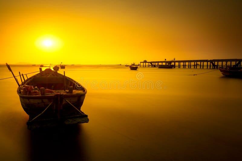 Bateau de pêche avec le coucher du soleil images stock