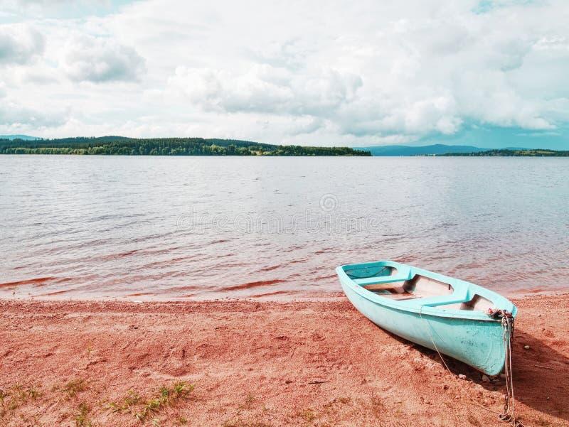 Bateau de pêche bleu ancré sur le sable de plage du lac Niveau doux image stock