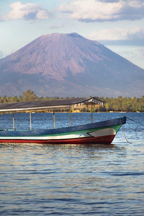 Bateau de pêche devant le volcan sur la mer et le paysage image stock