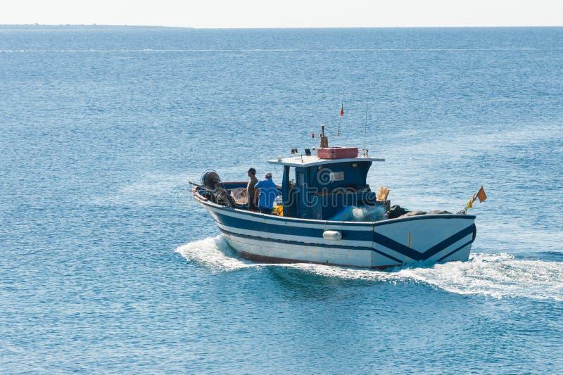 Bateau de pêche en action en mer photos stock