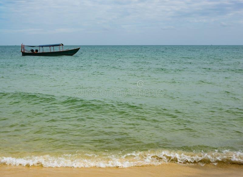 bateau de pêche en bois dans les eaux bleues et vertes du Cambodge photos stock