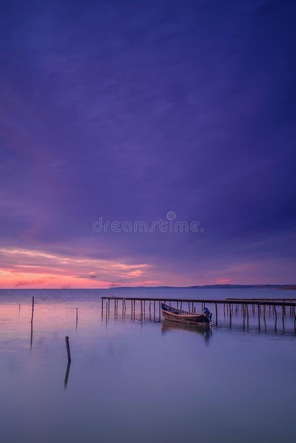 Bateau de pêche motorisé près d'un ponton capturé avant lever de soleil avec des ombres des oiseaux de vol dus à la longue exposi photographie stock