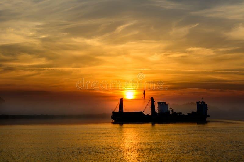 Bateau de pêche quittant le port sur un fond brumeux horizont photos stock
