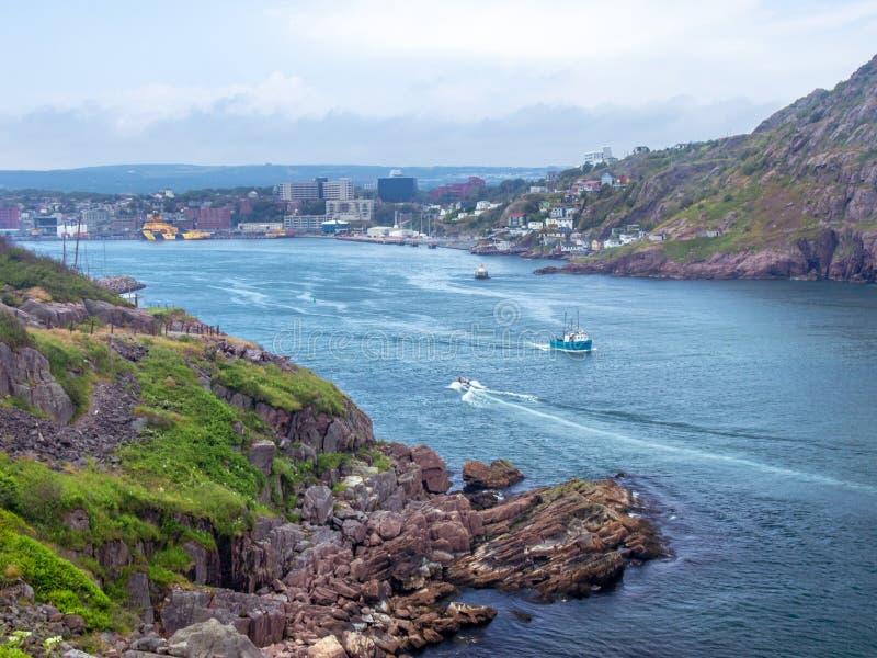 Bateau de pêche quittant un port en ` s de St John image libre de droits
