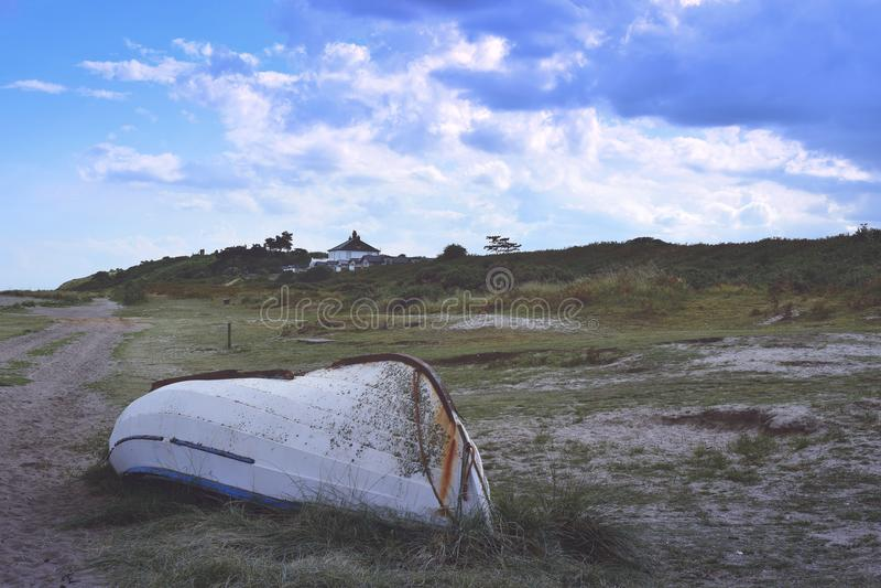 bateau de pêche retourné sur le rivage proche de bruyère photographie stock