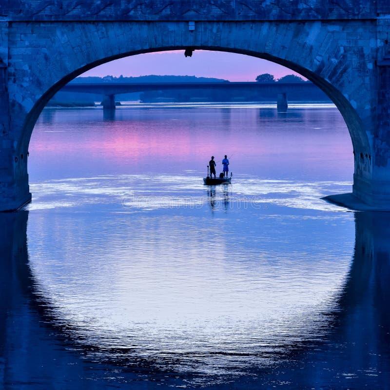 Bateau de pêche sous la voûte d'un pont dans un coucher du soleil coloré photos libres de droits