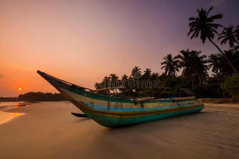 Bateau de pêche sur la plage au coucher du soleil Le Sri Lanka image stock