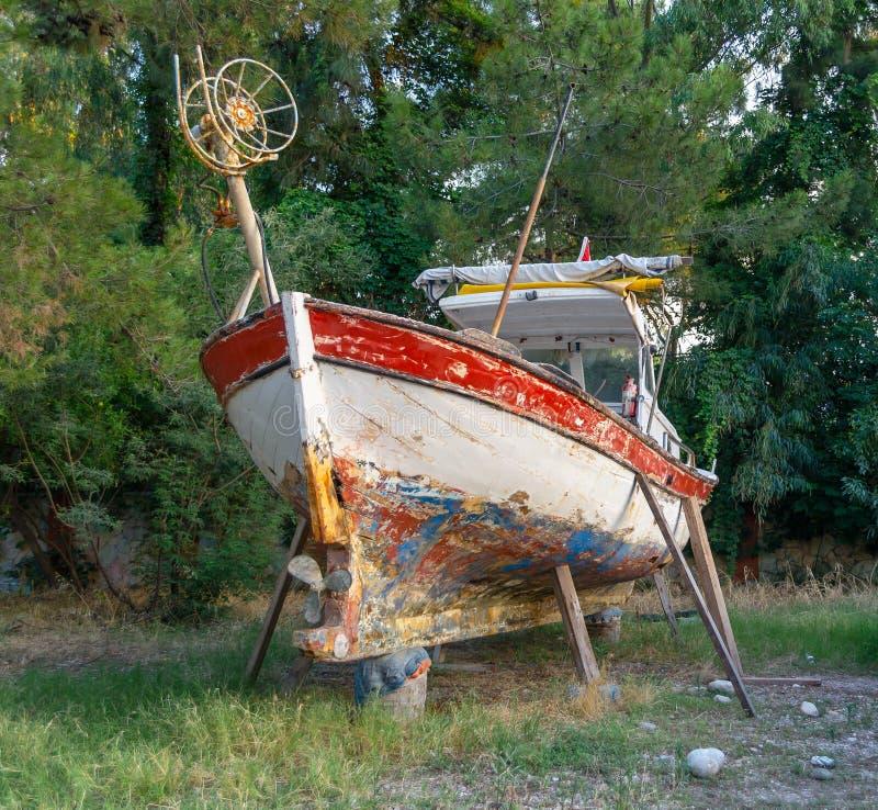 Bateau de pêche sur le rivage à réparer dans les bois image stock