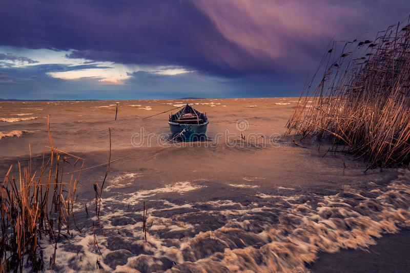 Bateau de pêche sur un lac un jour venteux pendant une tempête attachée jusqu'au rivage contre les nuages dramatiques et les gran photo stock