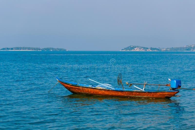 Bateau de pêche thaïlandais sur les vagues de la mer azurée Bateau de pêche de moteur sur le fond des îles photo stock