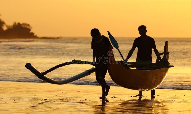 Bateau de pêcheur avec deux pêcheurs chez Bali, Indonésie pendant le coucher du soleil à la plage photos libres de droits
