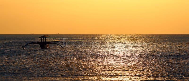 Bateau de pêcheur sans pêcheur chez Bali, Indonésie pendant le coucher du soleil à la plage photos stock