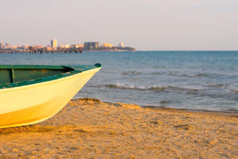 Bateau de pêcheur sur le sable près de la mer, tir de coucher du soleil image stock