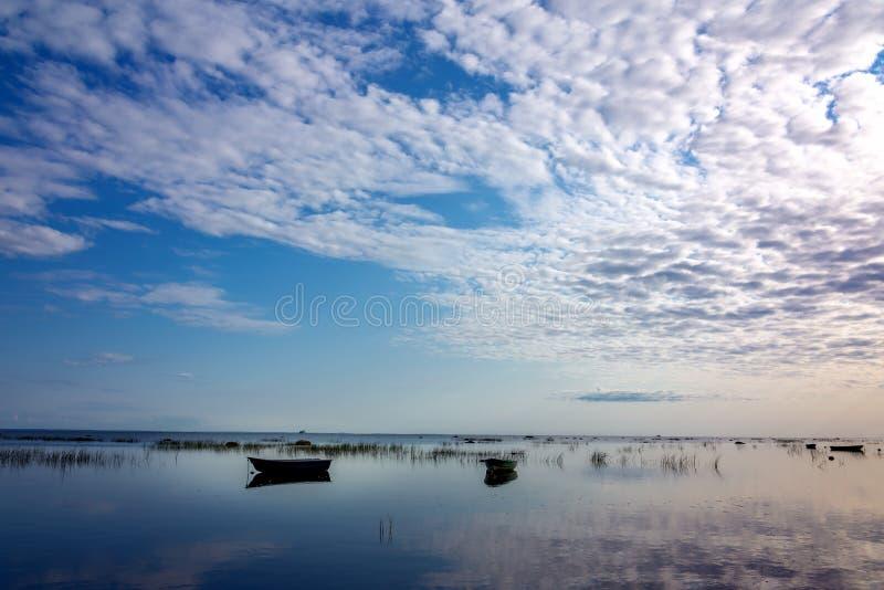 Bateau de p?che dans le lac clair au coucher du soleil Vue sc?nique image stock
