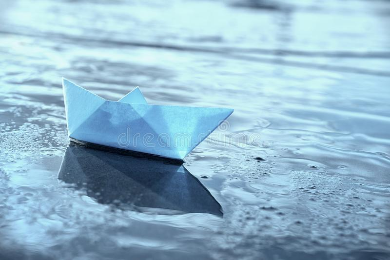 Bateau de papier bleu isolé en eau peu profonde photos libres de droits